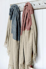 Hali Blue and Hali Red linen throws hanging on wall hooks.
