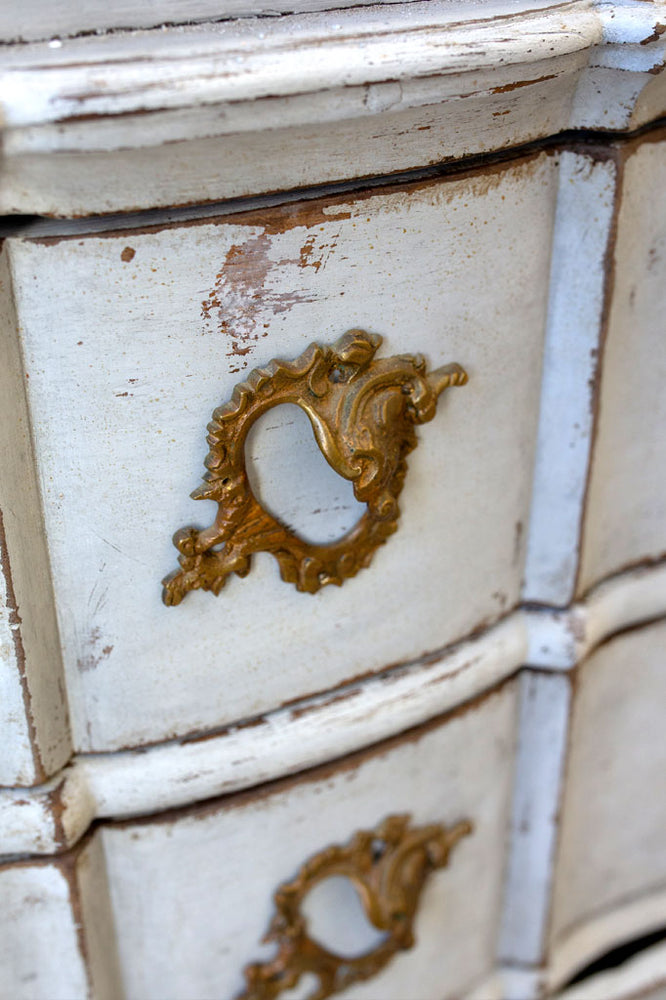 The drawer handles of the large white Gustavian bureau.