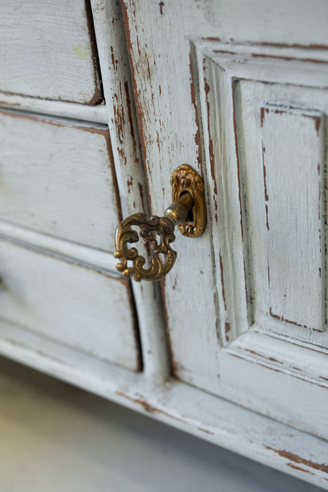 Ornate key in the lock of an internal cupboard of this stunning white Gustavian bureau.
