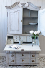Dressed white Gustavian bureau with flowers and crockery.
