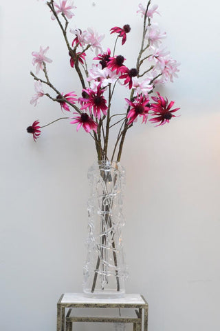 Modernly designed blown glass Miro vase with pink flowers inside on a stool