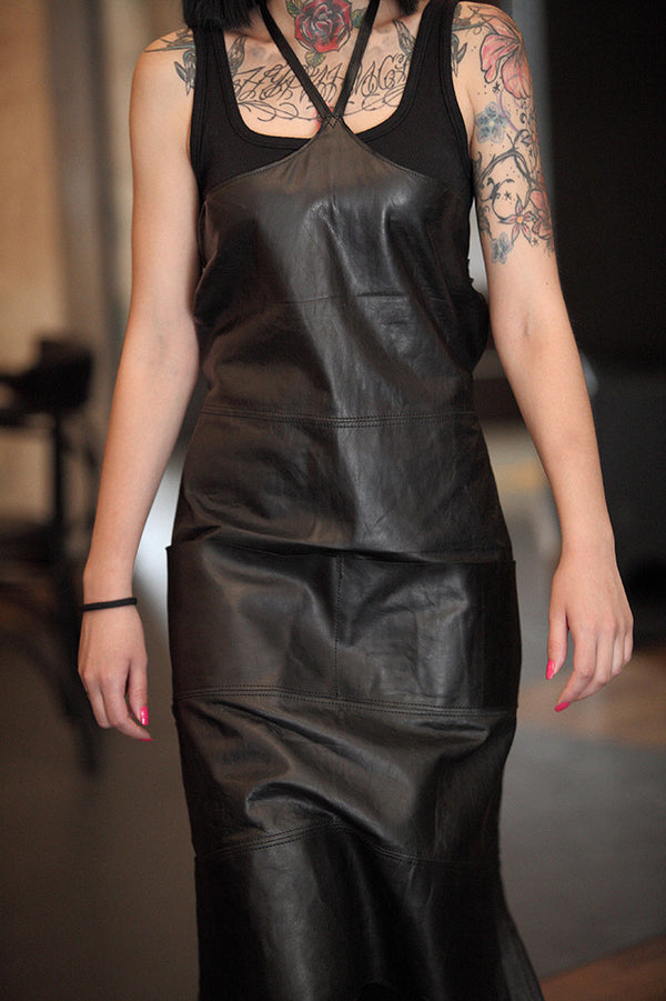 Tattooed woman wearing black leather necklace apron.