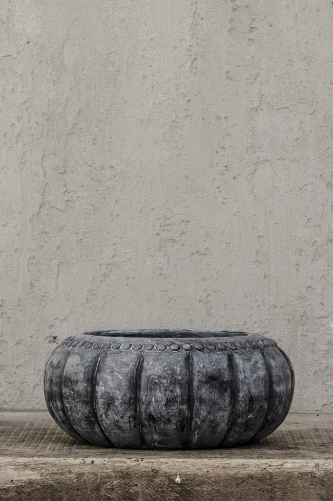 Carved stone bowl, against concrete wall.