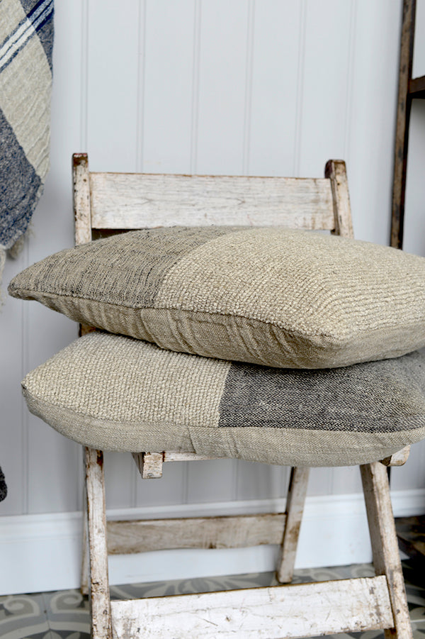 A pair of Kabuli linen cushions in natural and grey.