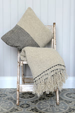 A kabuki cushion, shown with matching natural throw.