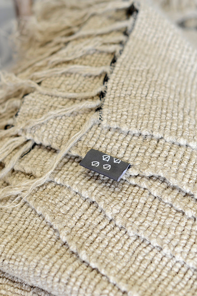 Close up of the natural Kabuli linen throw and Cotswold Grey label.