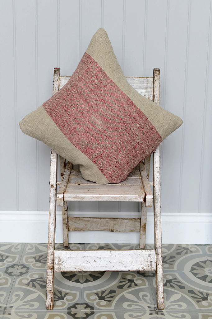 Cotswold Grey Hali cushion in red pictured on top of an indian chair