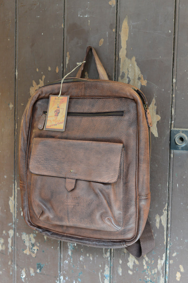 Avirex Leather Military Style Brown Backpack Bag, hanging on wooden door.