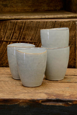 A collection of Broste Nordic Sand handless mugs.