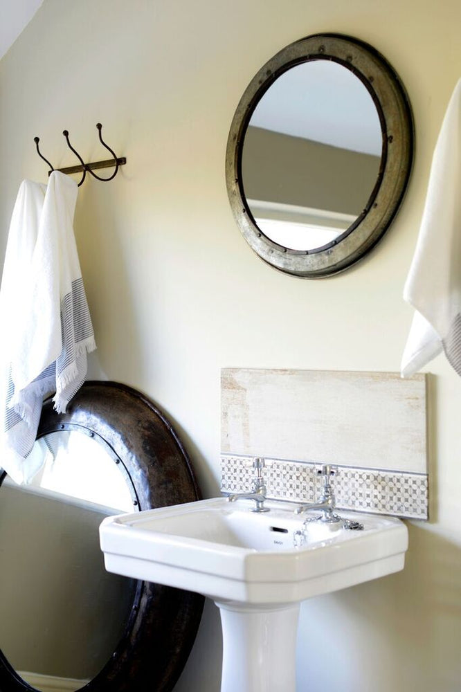 Small hammered iron mirror hanging in a bathroom above the sink