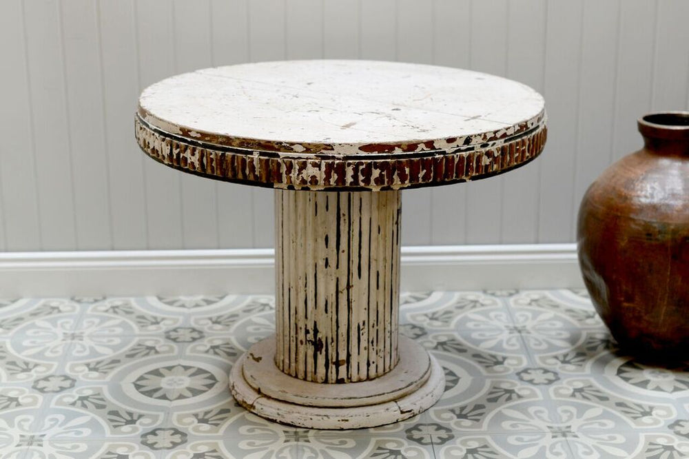 White washed distressed coffee table stood next to the brass pot