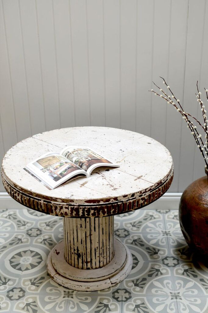 Lifestyle shot showing our white distressed coffee table with an open book on next to a brass pot