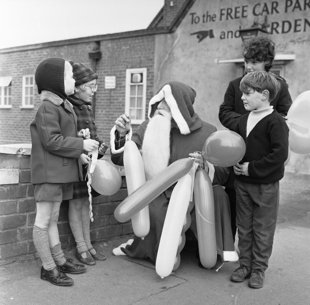 Detail of Father Christmas seen here handing out balloons in Tilhurst by Staff