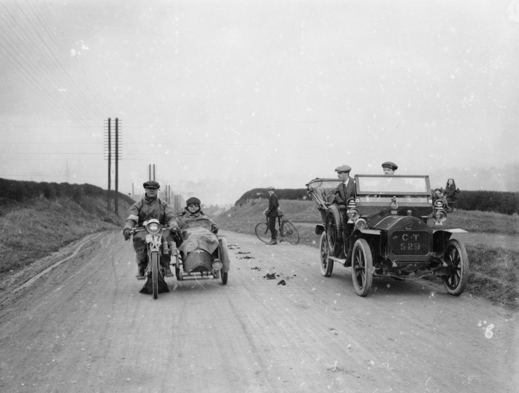 Detail of A motorcycle and sidecar passing a car and cyclist on the road by Unknown