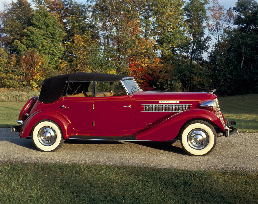 A 1936 Auburn 852 car on a gravel driveway in the autumn sunlight by Unknown