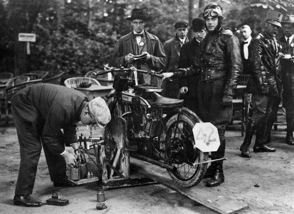 Detail of Karl Burlage having his Norton bike weighed for a TT competition by Unknown
