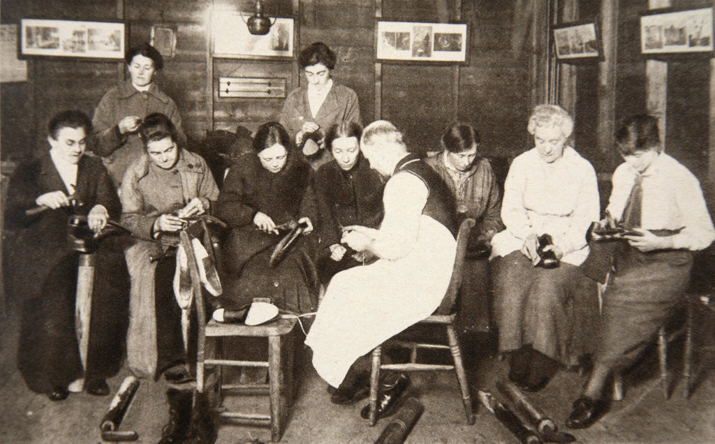 Detail of A group of women receive a lesson in boot repairing by S and G