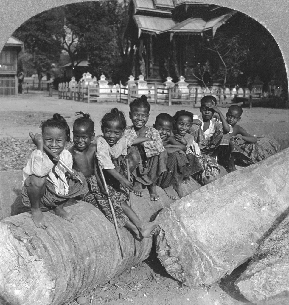 Detail of Burmese children sitting on a palm log, Burma by Stereo Travel Co