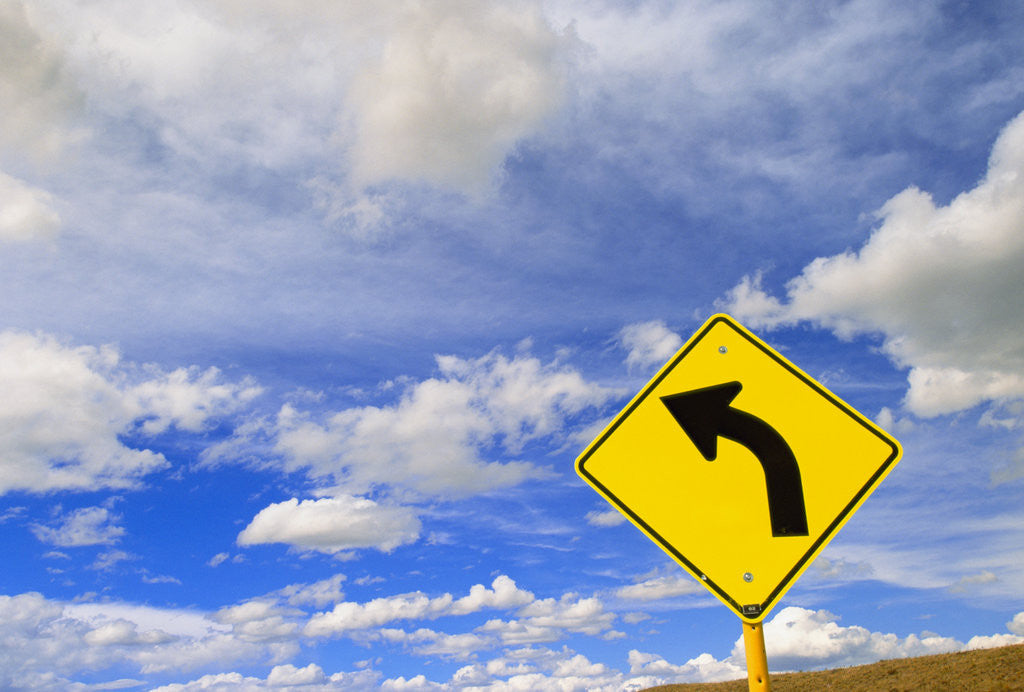 Detail of Curve Road Sign on Highway Against Sky by Corbis