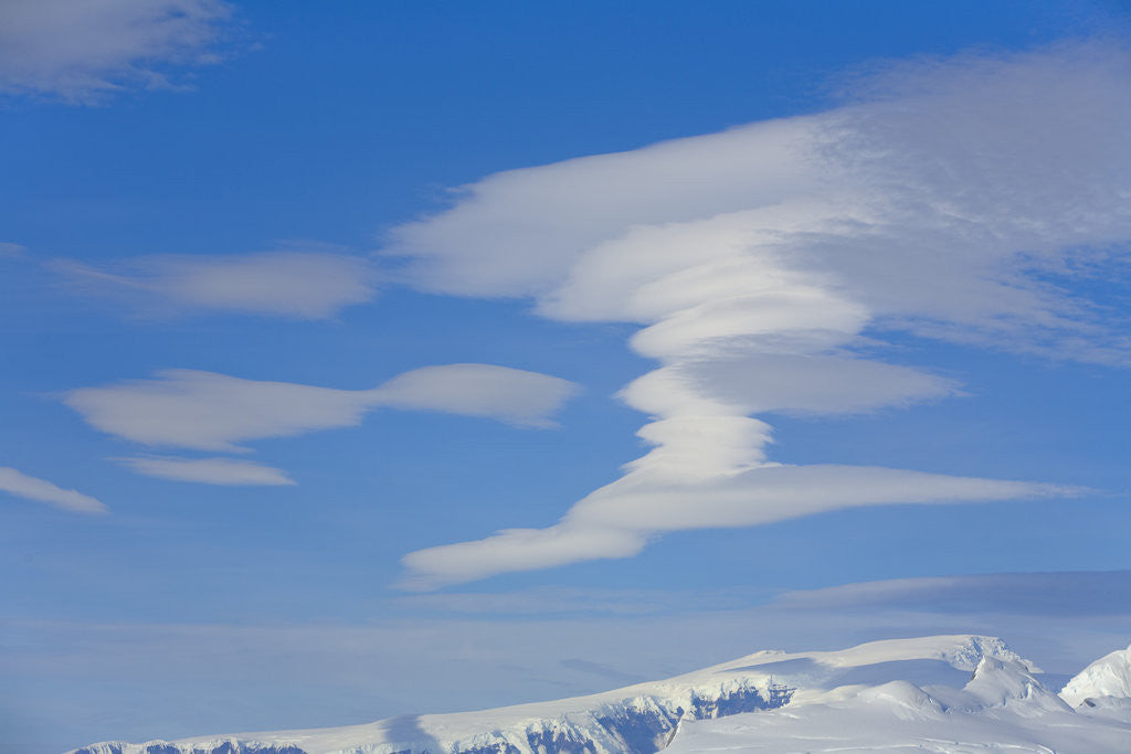 Lenticular Clouds Floating above Snow-covered Glacier