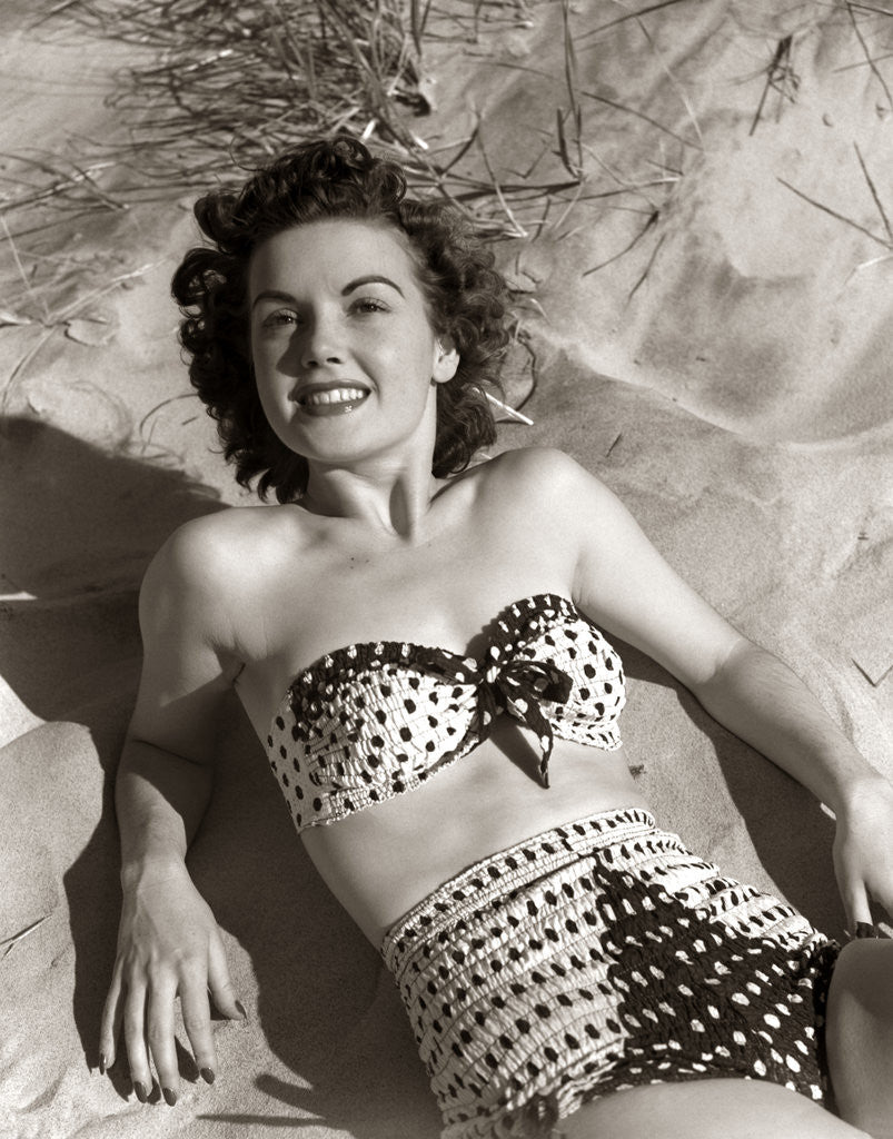 Detail of 1950s Brunette Woman Wear Polka Dot Two Piece Bathing Suit Laying On Sand by Corbis