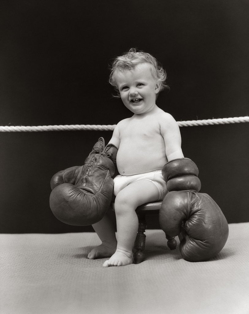 Detail of 1930s Baby Seated On Stool In Boxing Ring Wearing Oversized Boxing Gloves Wearing Diaper by Corbis