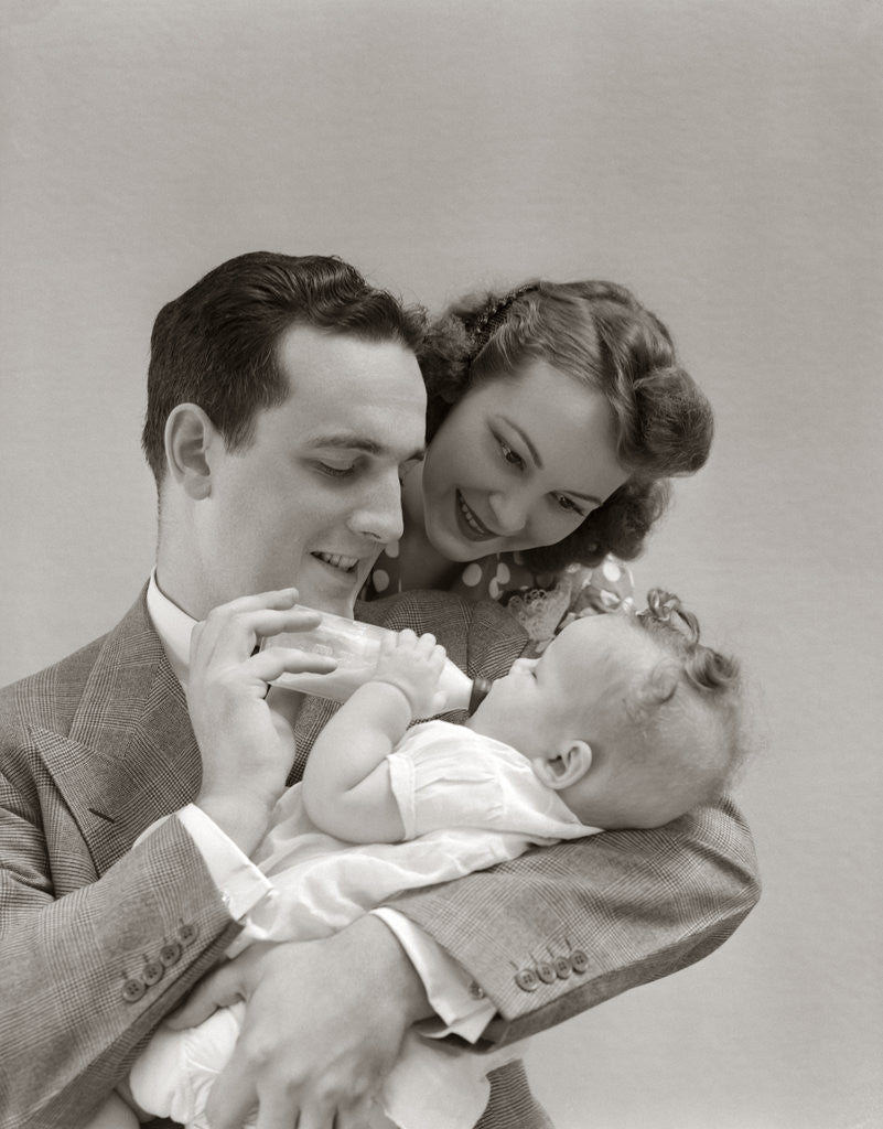 Detail of 1940s Father Cradling Baby Daughter Feeding Her Bottle With Mother Looking Over His Shoulder by Corbis
