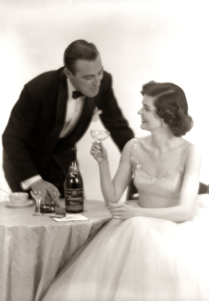 Detail of 1950s Formal Dress Couple Man In Tuxedo Woman Wearing Gown Holding Champagne Glass by Corbis