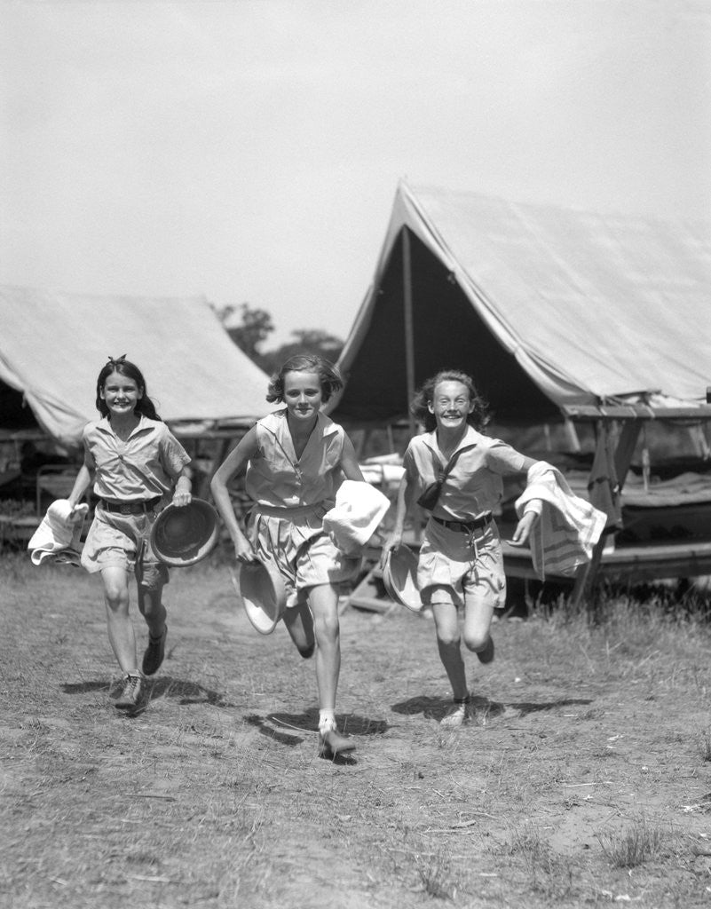 Detail of 1930s Three Teen Girls Wearing Camp Shorts and Shirts Running From Tents While Holding Towels and Wash Basins by Corbis