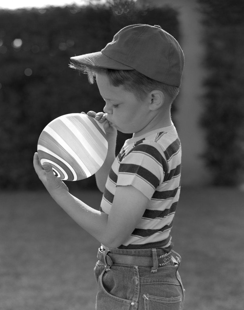 Detail of 1950s Side View Of Boy In Baseball Cap and Striped T-Shirt Blowing Up Swirled Balloon by Corbis
