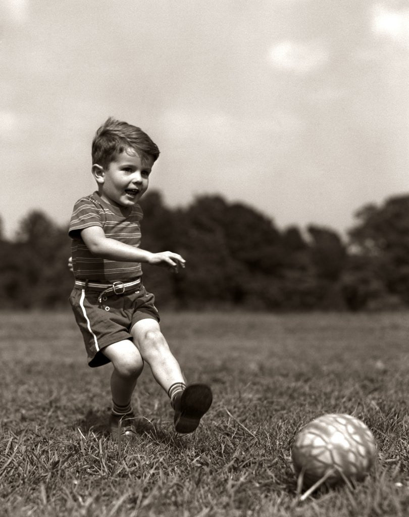 Detail of 1940s Boy Kicking Ball In Grassy Field by Corbis