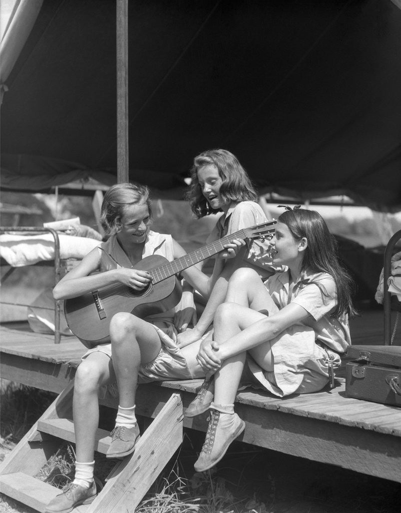 Detail of 1930s Three Girls At Summer Camp Having Sing-Along One Playing Guitar by Corbis