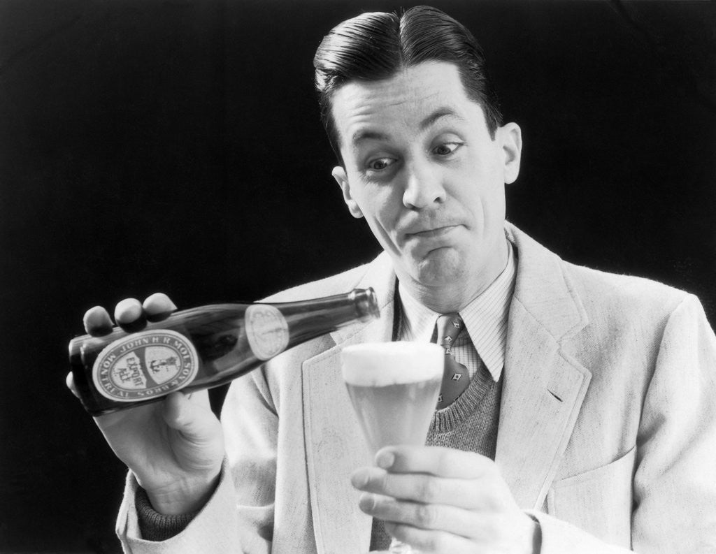 Detail of 1930s Man Pouring Beer From Bottle Into Glass Look Of Anticipation Wearing Suit Tie Sweater by Corbis