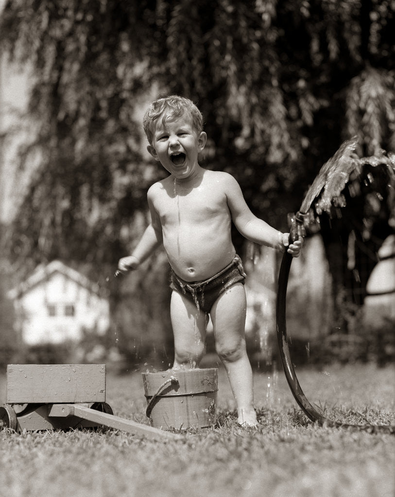Detail of 1940s 1950s Wet Young Boy Toddler Outside Playing With Water Hose by Corbis