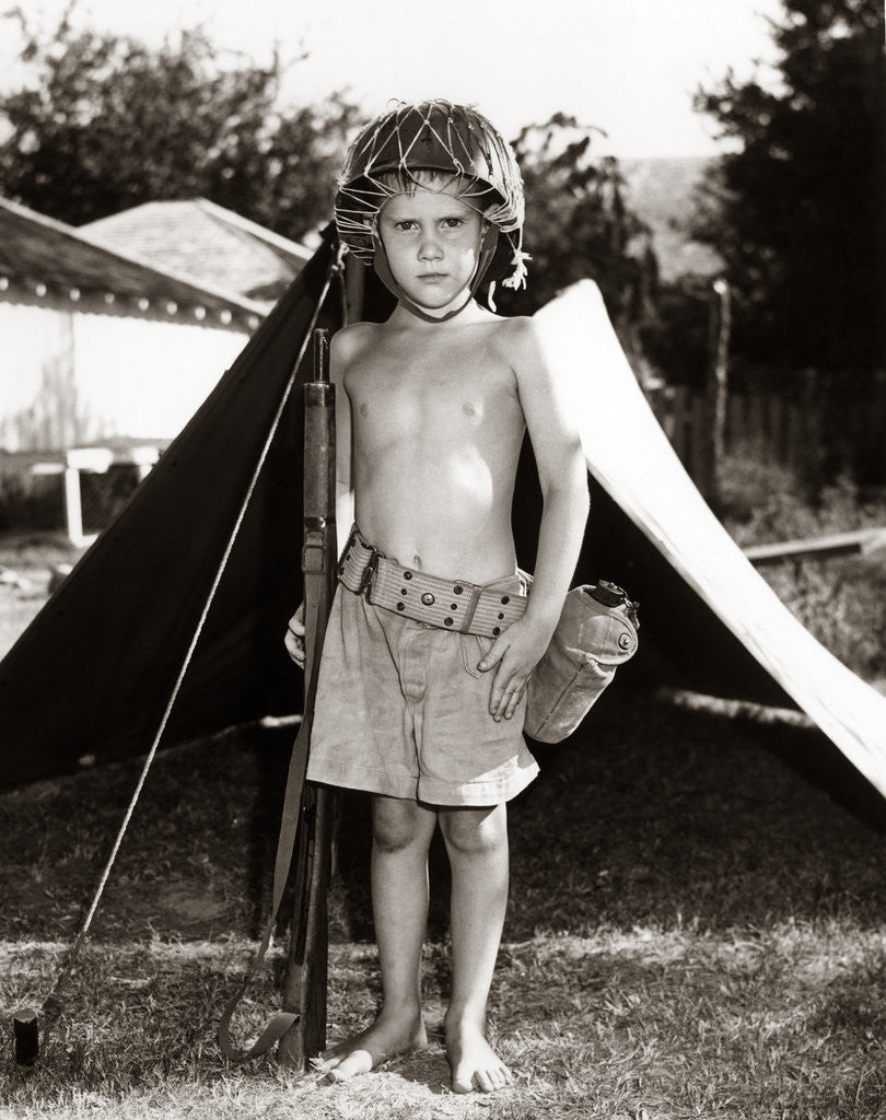 Detail of 1950s Boy Playing Soldier Standing With Rifle Helmet Canteen Tent by Corbis
