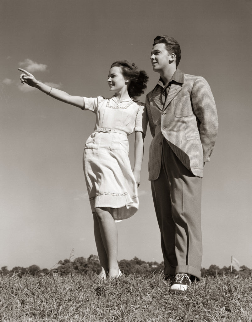 Detail of 1940s Teenage Couple Standing Together Outdoors Girl Pointing by Corbis