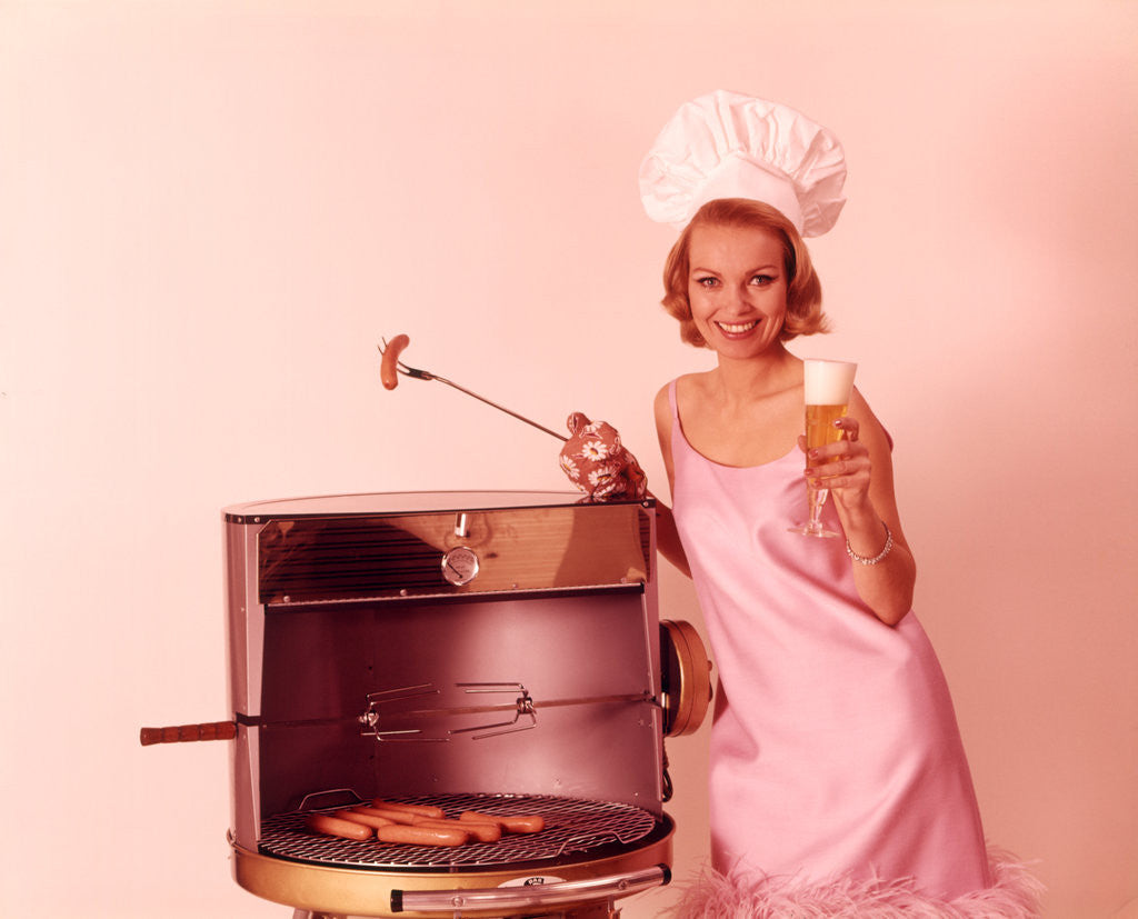 Detail of 1960s Woman Wearing Pink Party Dress And Chef Hat Grilling Hot Dogs Drinking Beer by Corbis
