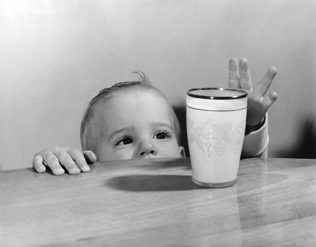 Detail of 1950s Toddler Reaching Up To Table To Grab Milk Glass by Corbis