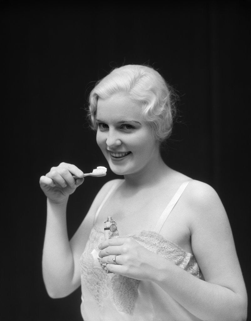 Detail of 1930s Woman Holding Tooth Paste And Tooth Brush Btushing Teeeth by Corbis