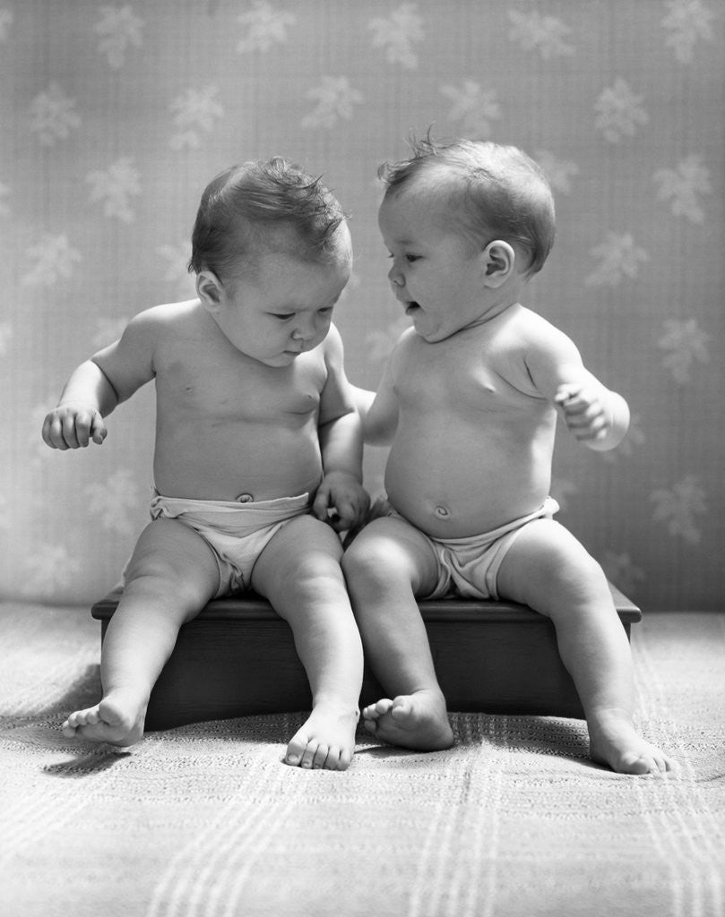 Detail of 1930s 1940s Twin Babies Wearing Diapers Together Sitting On A Bench Side By Side Studio by Corbis