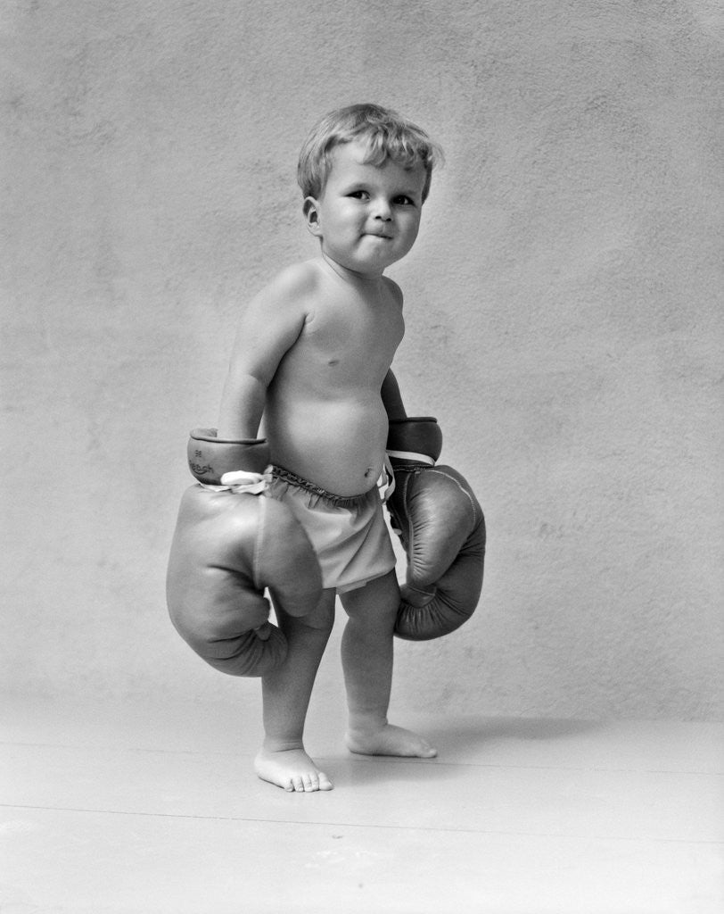Detail of 1930s Baby Boy Toddler Wearing Oversize Boxing Gloves by Corbis