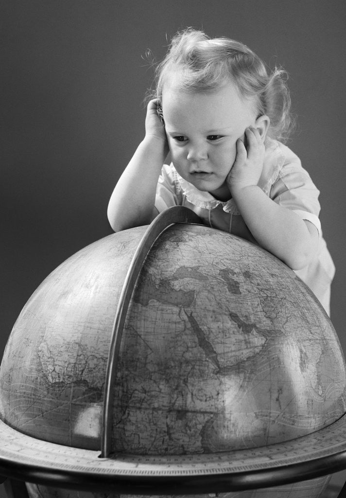 Detail of 1940s Baby Looking At Leaning On Globe Of Earth by Corbis