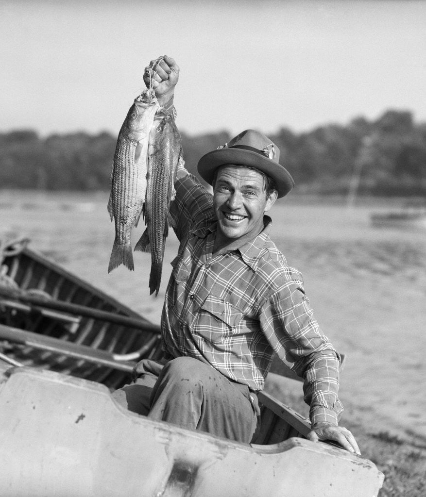 Detail of 1940s 1950s Happy Man Fishing From A Rowboat Holding Up Fish Just Caught With Pride by Corbis