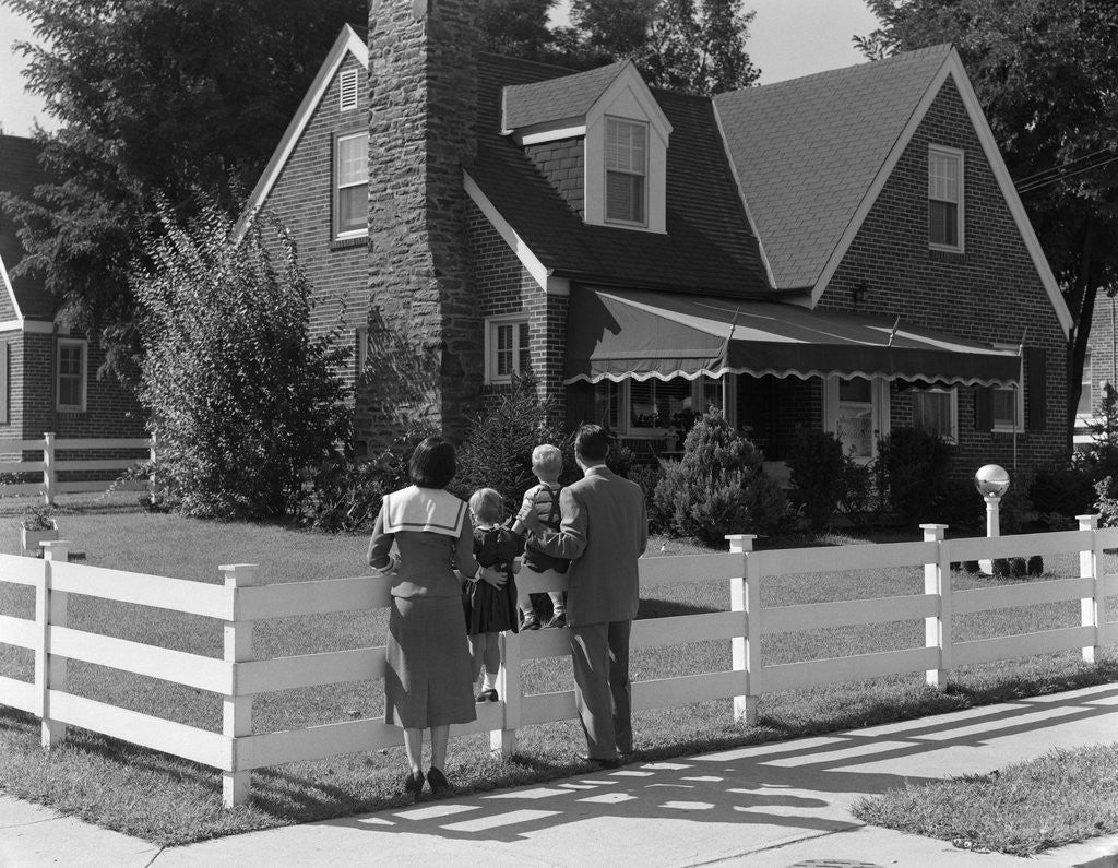 Detail of 1950s Family Standing By White Fence Looking At Brick House by Corbis