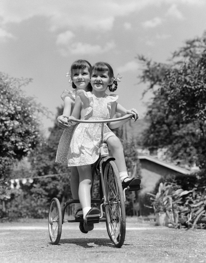 Detail of 1940s Twin Girls Riding Outside On Tricycle by Corbis