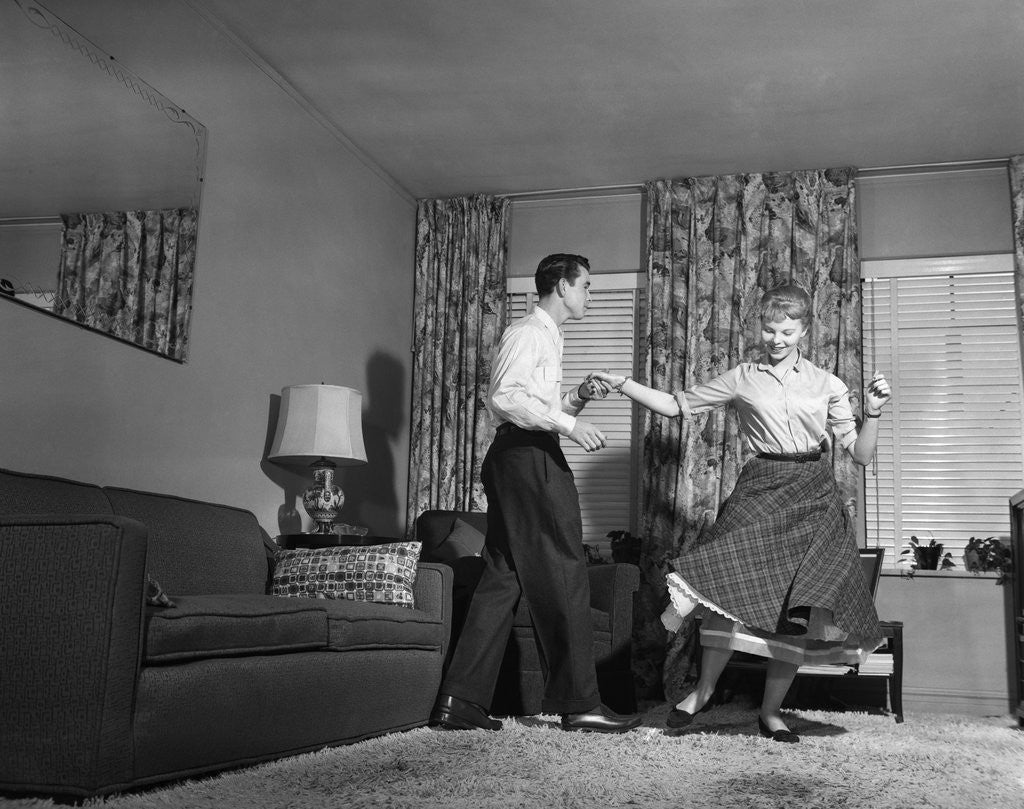 Detail of 1950s Teen Couple Doing Jitterbug Rock And Roll Dance In Living Room Man Woman Boy Girl by Corbis