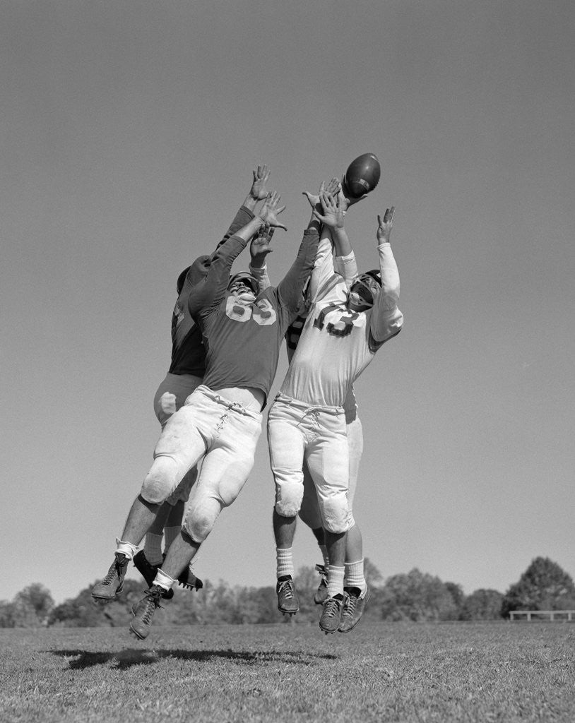 Detail of 1960s Three Football Players Reaching To Catch Ball by Corbis