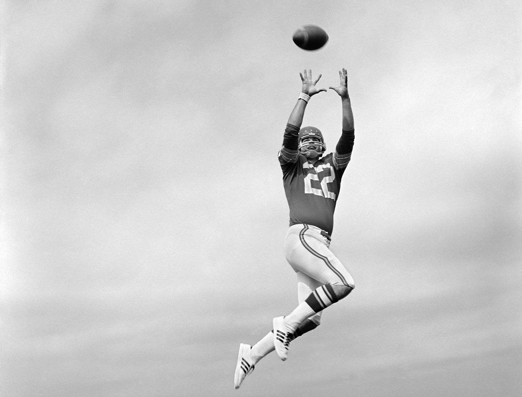 Detail of 1970s Player Jumping To Catch Football Pass by Corbis