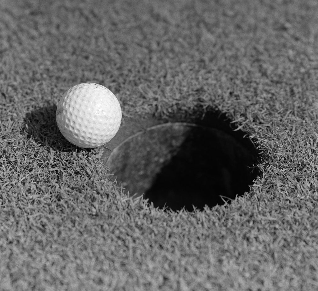 Detail of 1950s Close-Up Of Golf Ball On Green On Very Edge Of Cup by Corbis