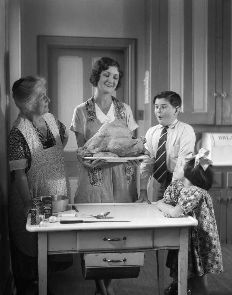 Detail of 1920s 1930s Mother Grandmother Boy Girl Cooking Turkey In Kitchen by Corbis